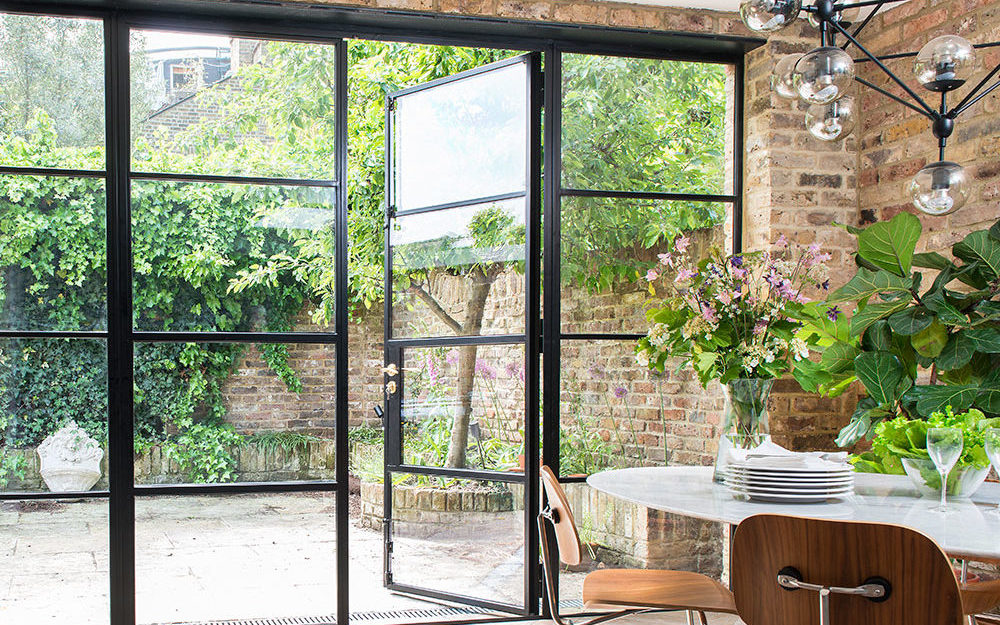 An architecturally designed dining room with glass doors to outside space