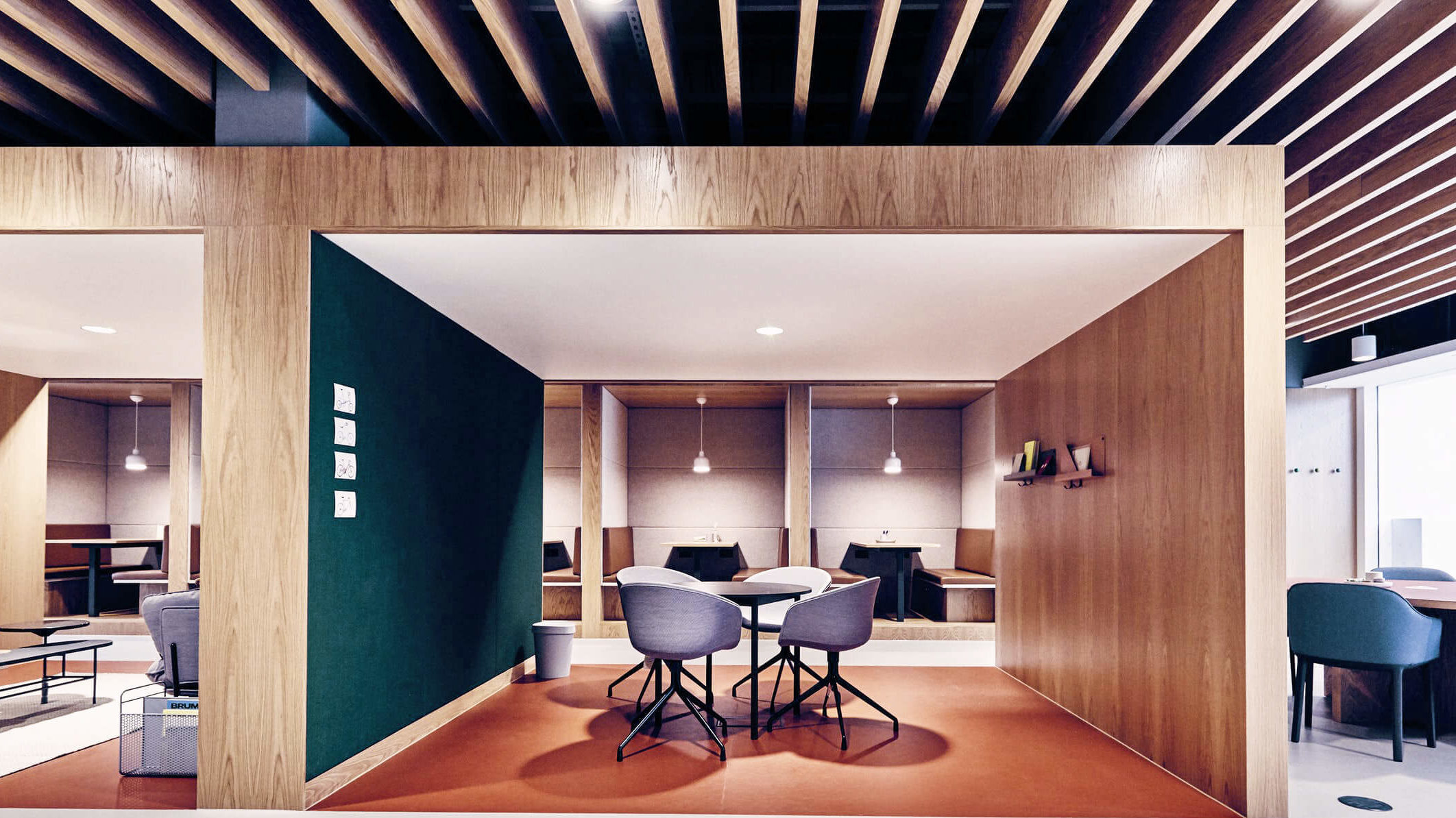 An architecturally designed office breakout space with desks and booths